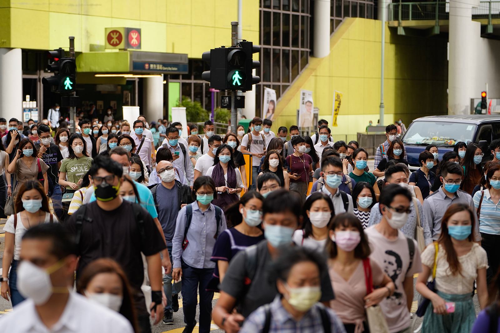 Pedestrians wearing protective masks walk across a road in Hong Kong, China, on July 10.