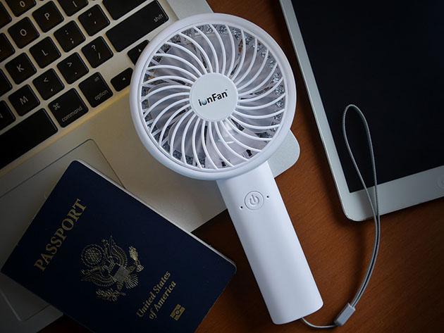 Een ventilator die op laptop naast een paspoort rust