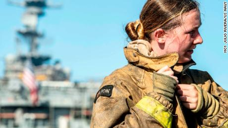 Een matroos trekt haar brandweer-ensemble uit na het bestrijden van een brand aan boord van het amfibische aanvalsschip USS Bonhomme Richard.