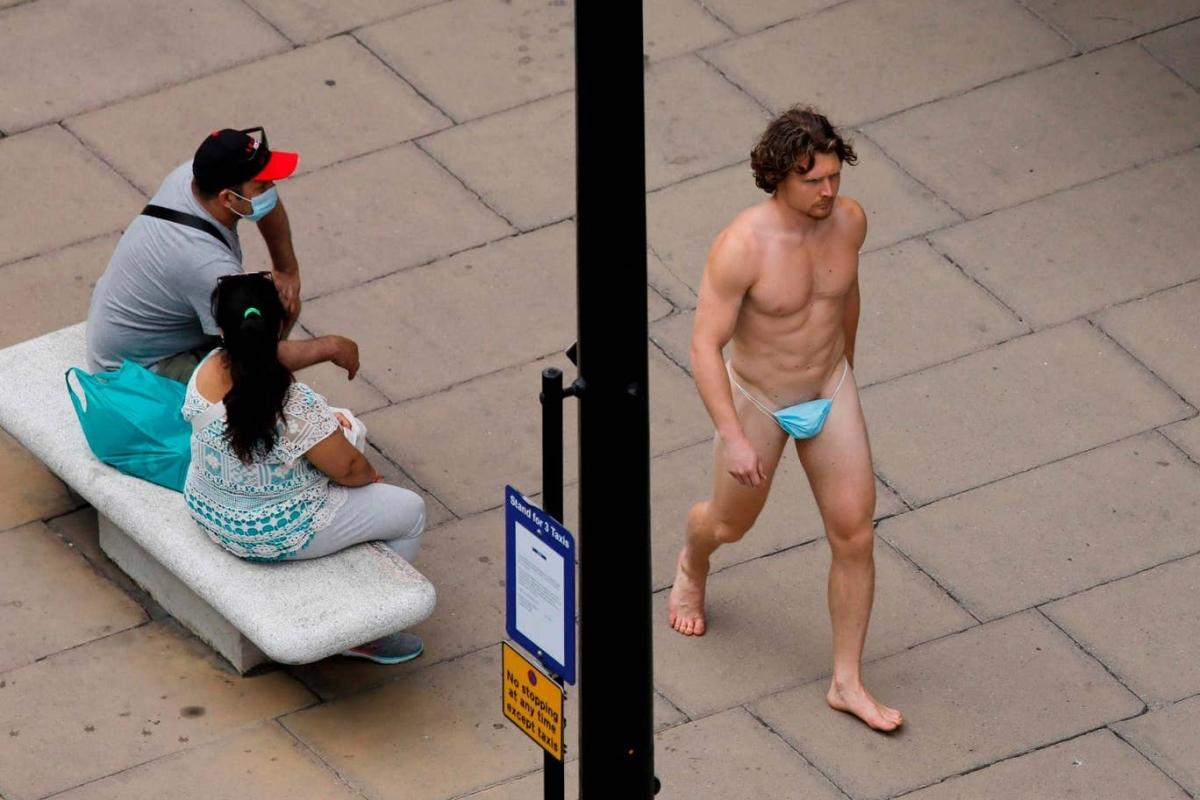 A man wearing a surgical mask as G-string walks past a woman, as the spread of the coronavirus disease (COVID-19) continues, on Oxford Street in London, Britain July 24, 2020. REUTERS/Simon Dawson