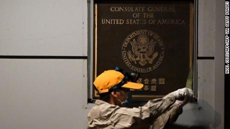 Een arbeider probeert een plaquette op de muur te verwijderen buiten het Amerikaanse consulaat in Chengdu, in het zuidwesten van China.
