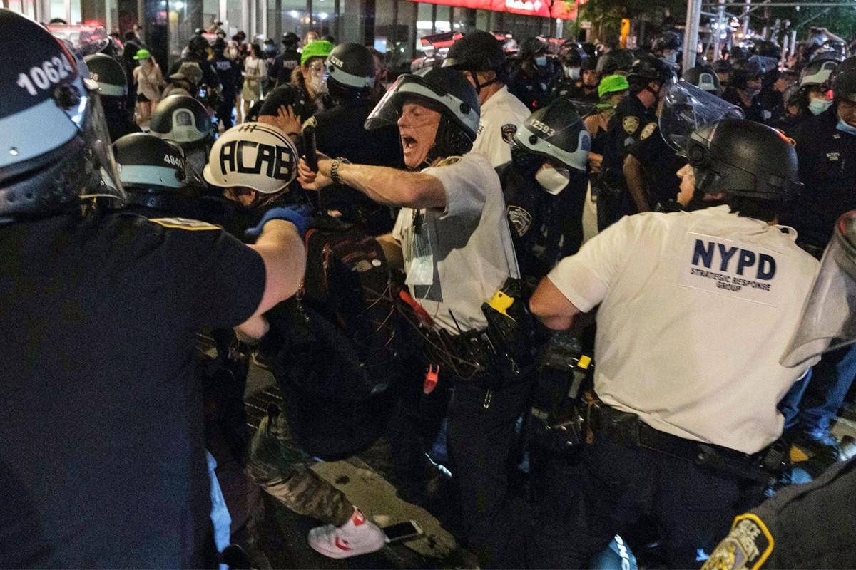 Opstandelingen richten zich op NYPD-auto's, lichtbranden in een chaotisch stadsgezicht
