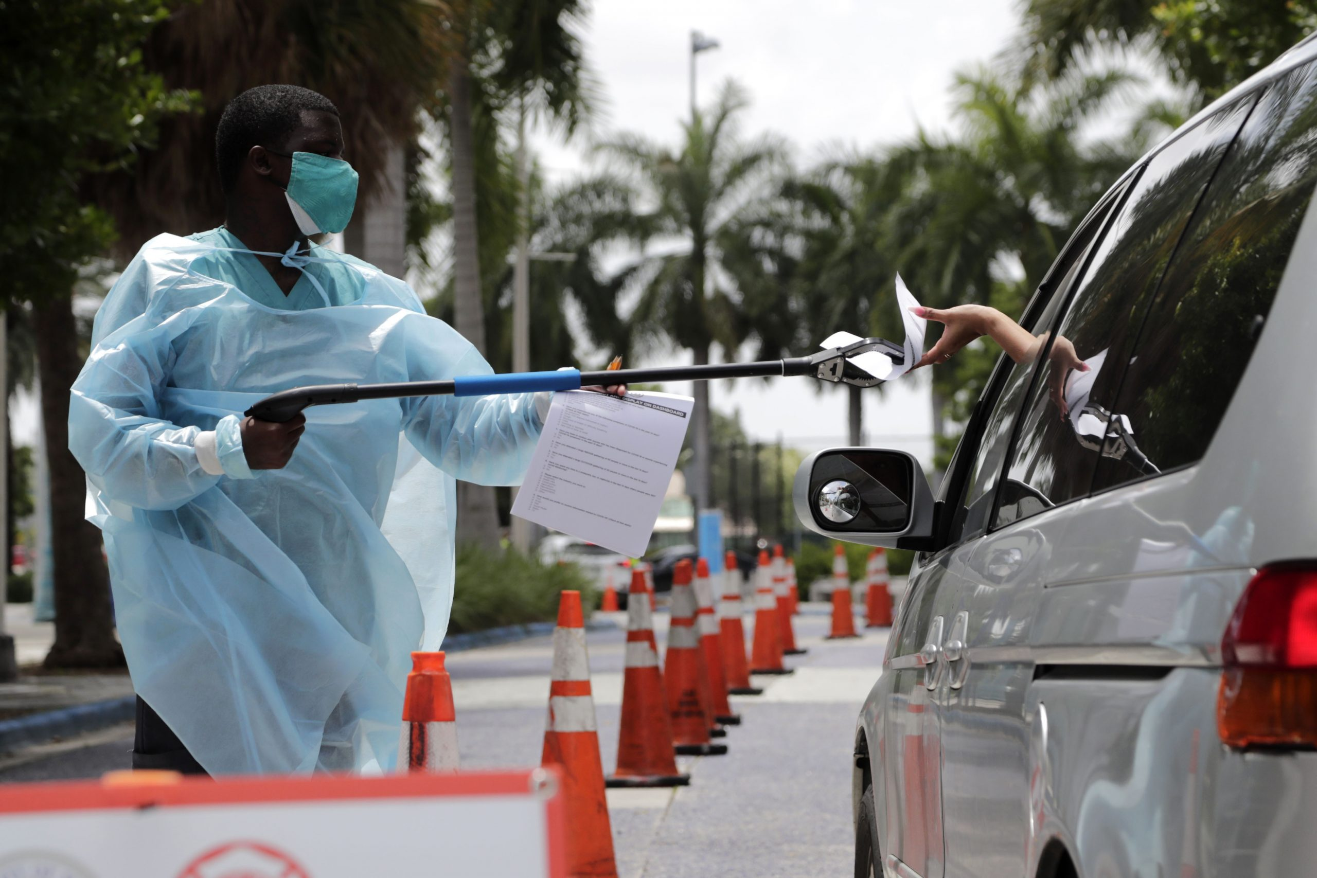 A health care worker passes paperwork to someone at a Covid-19 testing site in Miami on July 27.