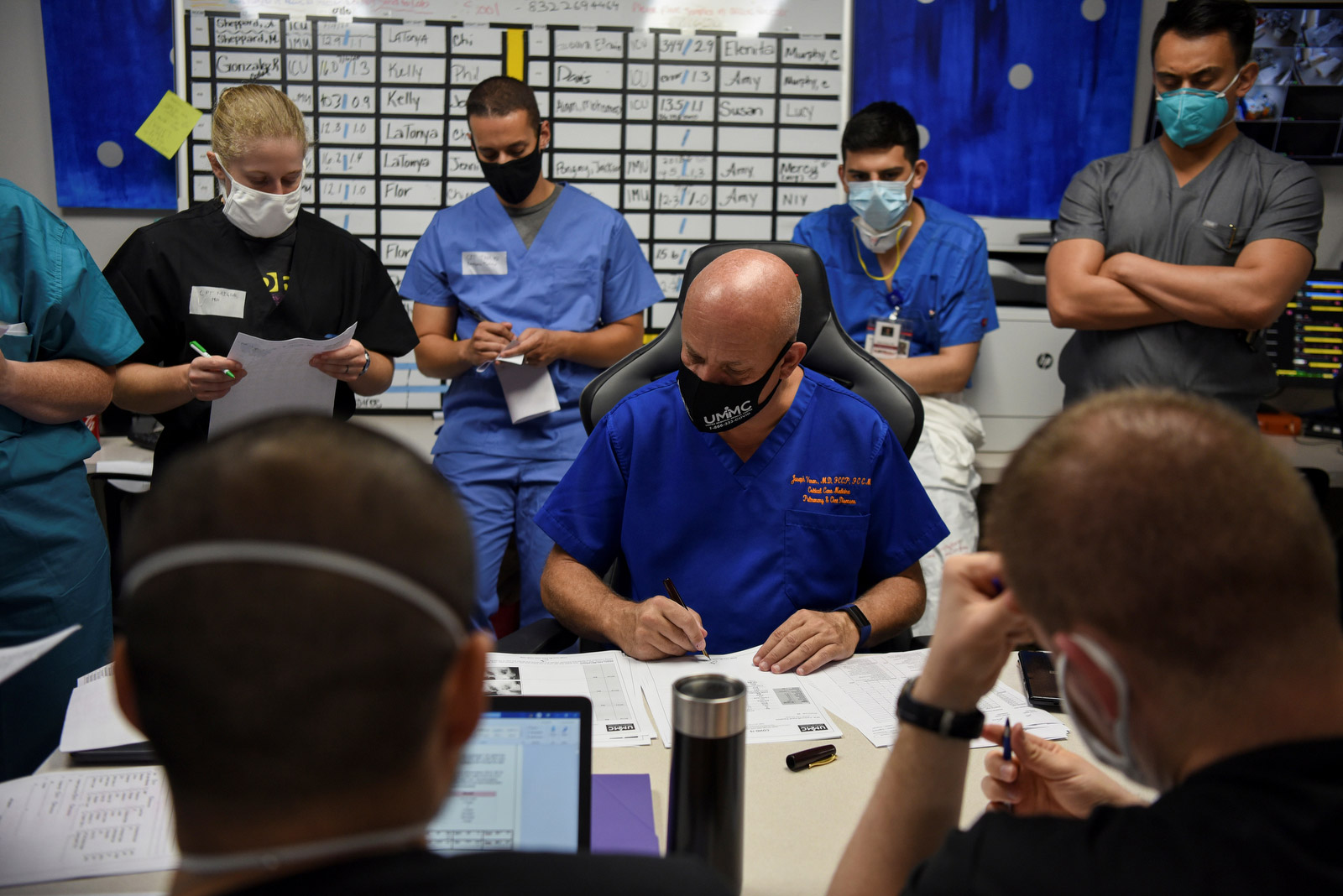 Varon en zijn team nemen tijdens een dagelijkse vergadering de patiëntendossiers door.