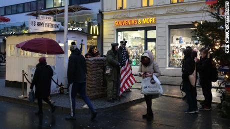 Toeristen maken foto's van acteurs verkleed als soldaten bij voormalig Checkpoint Charlie in Berlijn, waar Amerikaanse en Sovjet-tanks elkaar in de eerste jaren van de Koude Oorlog confronteerden.