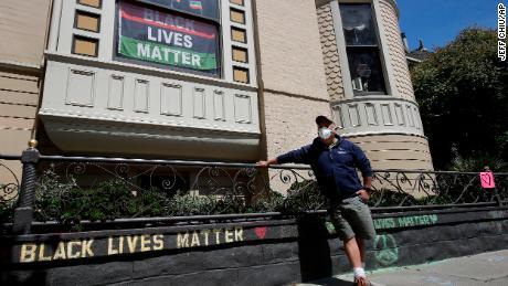 James Juanillo poseert met een krijtbericht dat op 14 juni 2020 buiten zijn huis in San Francisco, Californië is geschreven.