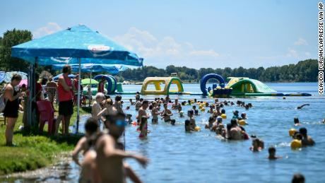 In Italië wordt het weer normaal. Mensen zwemmen op 12 juli in een kunstmatig meer in Milaan.