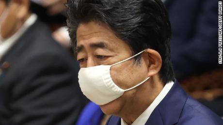 De Japanse premier Shinzo Abe draagt een gezichtsmasker uit bezorgdheid over de verspreiding van het coronavirus, spreekt tijdens een zitting van de begrotingscommissie in het lagerhuis van het parlement in Tokio op 10 juni 2020.