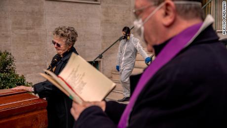 Een priester met een masker zegent op 27 maart een kist op de binnenplaats van een gebouw in Napels, Italië.